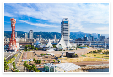 青空と山々を背景に高層ビルやタワーが立ち並ぶ神戸の風景