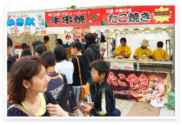 食べ物の屋台とその側を通るイベントの参加客
